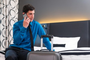 Man telephoning at arrival in hotel room